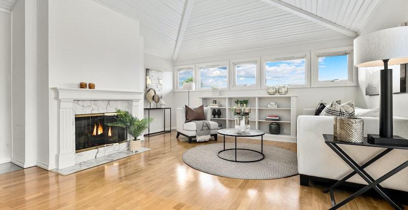 Luftig stue med peis. integrert seksjon og vinduer mot fjorden og mot vest