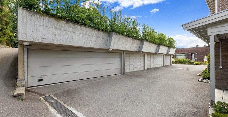 Gårdsplass med garasjerekke hvor denne leiligheten disponerer en plass. I tillegg 2 biloppstillingsplasser for gjester