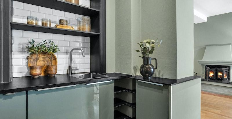 Kjøkkenet er praktisk designet med god benkeplass samt lagring i benkeskap, hyller og skuffer