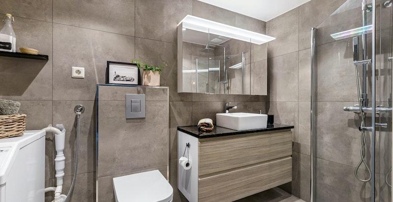 Lekkert baderom pusset opp i 2017 - Badet inneholder dusj på gulv med innfellbare glassvegger, vegghengt toalett og servantinnredning for oppbevaring - Varmekabler i gulv