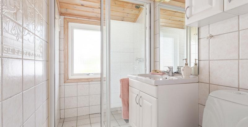Badet ligger i fin tilknytning til boligens soverom, og er ustyrt med wc, servantskap og dusj i hjørtne med skyvedører.