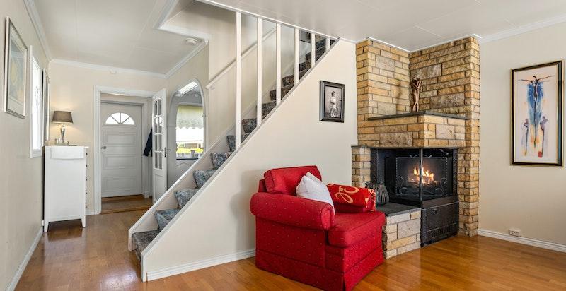 Stuen har en hyggelig peisinnsats med murt omramning som varmer godt.