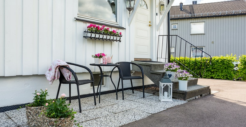 På fremsiddern av boligen ved inngangspartiet er det hyggelig plass til enklere utemøblement.