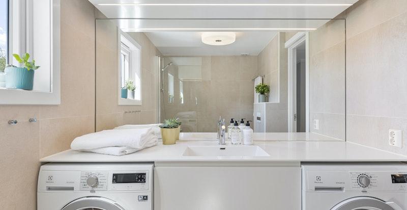 Praktisk innredet med plass til vaskemaskin og tørketrommel under benk