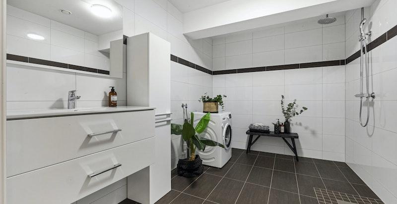 Flislagt bad i underetasje med opplegg til vaskemaskin.