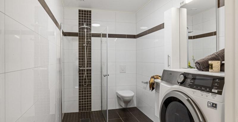 Flislagt bad med dusjhjørne og opplegg for vaskemaskin.