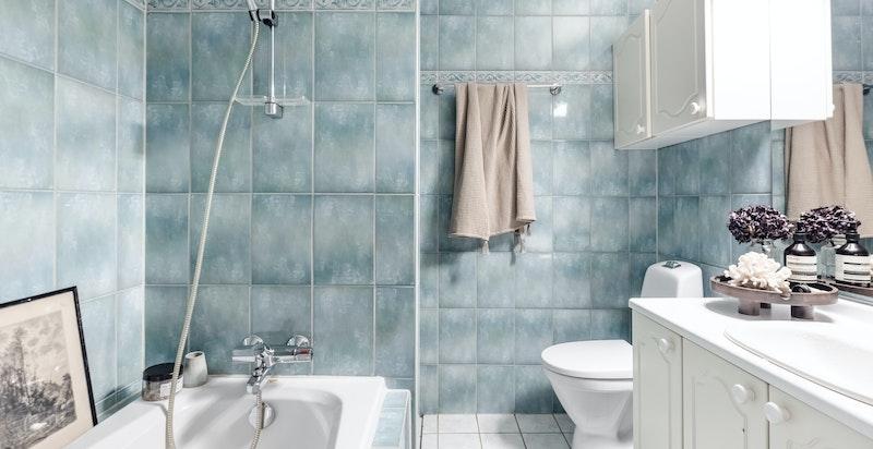 Baderom tilknyttet soverommet - Badet inneholder badekar, dusjnisje, toalett og servantinnredning for oppbevaring