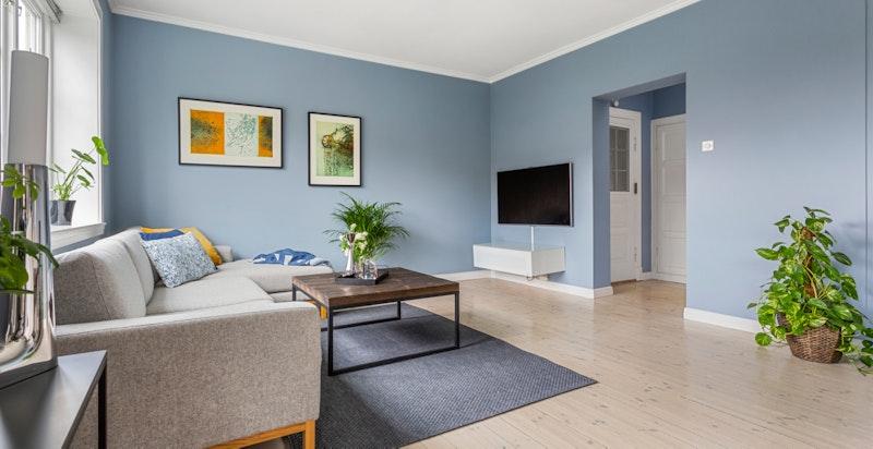 Stuen har slipte, originale tregulv og veggene er malt i en dus og fin blåtone.