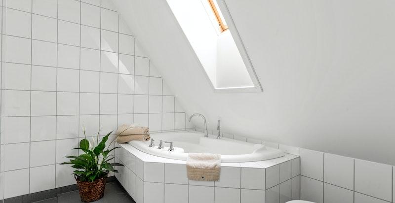 Badet er utstyrt med vegghengt wc, servant med skuffer under, dusj i hjørne med glassvegg og innmurt hjørnebadekar.