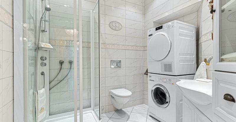Flislagt bad med varmekabler i gulv samt opplegg for vaskemaskin.