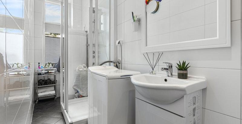 Flislagt bad i hybel med dusjkabinett og opplegg til vaskemaskin. Badet ble oppgradert i 2015.