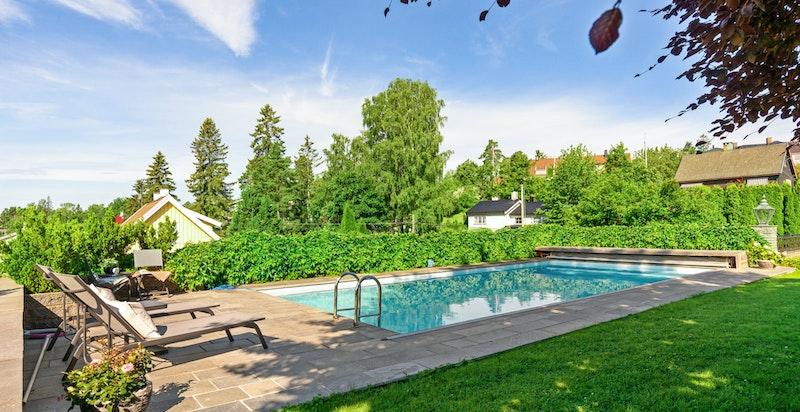 Svømmebasseng med herlig plen og terrasse