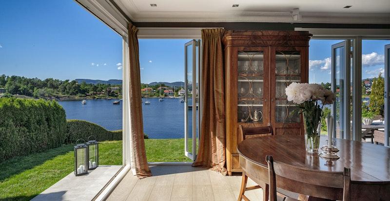 Stue med dører som kan åpnes helt opp og store glassflater