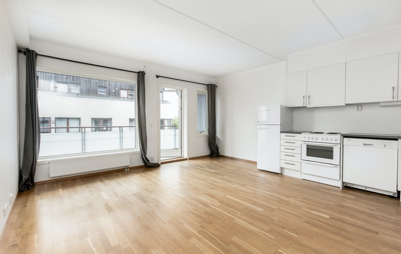 Stor og trivelig stue med kjøkken i åpen løsning. Utgang til solrik balkong
