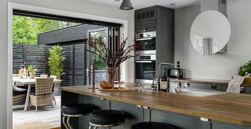 Kjøkkenøy med spiseplass, vask og armatur. Stor foldedør ut til solfyllt terrasse