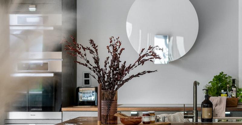 Kjøkkenet har integrerte hvitevarer som stekovn, dampovn, varmeskuff, oppvaskmaskin, kjøleskap og benkefryser.