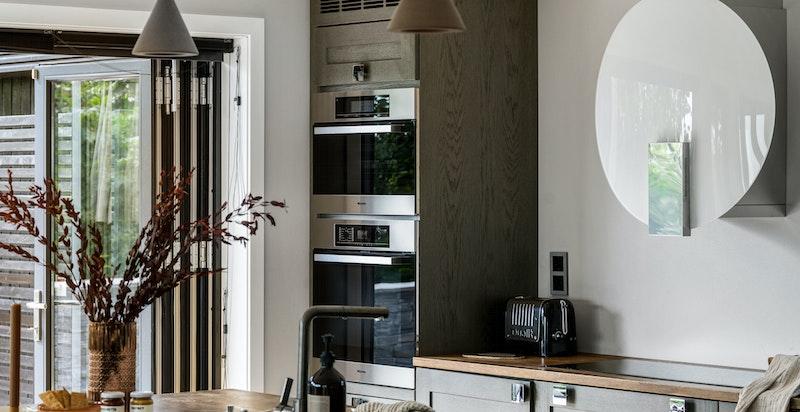 Kjøkkenet har integrerte hvitevarer som stekovn, dampovn, varmeskuff, oppvaskmaskin, kjøleskap og benkefryser. 90 cm bred induksjon koketopp.