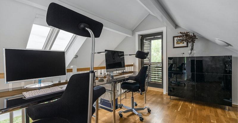 Perfekt for loftsstue, lekeplass eller, som her: hjemmekontor. Fransk balkong i enden og elektrisk betjent takvindu med meget fin utsikt