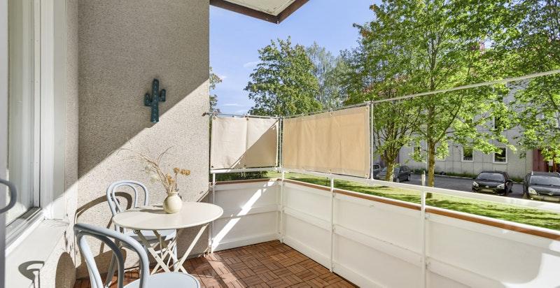 Rommelig sørvendt balkong (ca. 5,5 kvm) opphøyet fra terreng/gressplenen utenfor