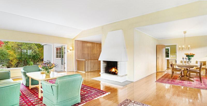 Romslig stue med peis og utgang til stensatt terrasseplatting og hage