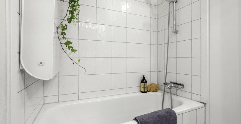 Badet er utstyrt med servant, stellebord og dusj i innmurt badekar.