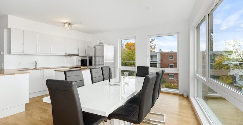 Pent HTH kjøkken med hvite glatte fronter på skuffer og over-/underskap