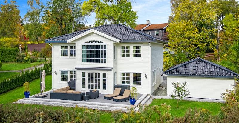 Boligen har flat tomt, pent opparbeidet med omkringliggende hage, gårdsplass og fin solrik uteplass på terrassen.