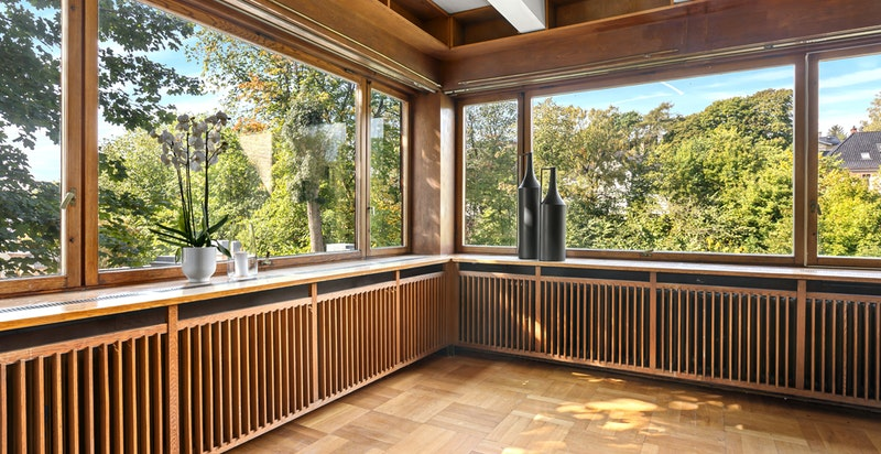 Bibliotek/stue har vindusflater i flere himmelretninger med grønt og hyggelig utsyn.