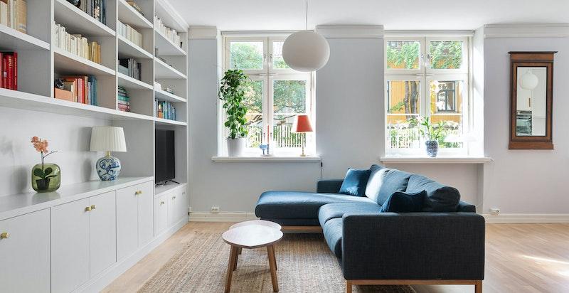 Stor stue med ny snekkerbygget bokhylle og store sørvestvendte vindusflater