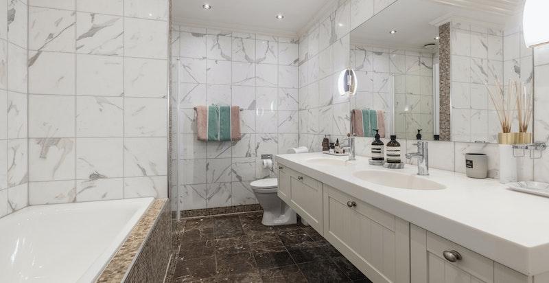 Stort flislagt baderom med badekar, dusj, servanter med skap og wc