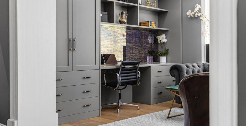 Detalj mot spesialtilpasset skap og bokhyller med hjemmekontorløsning