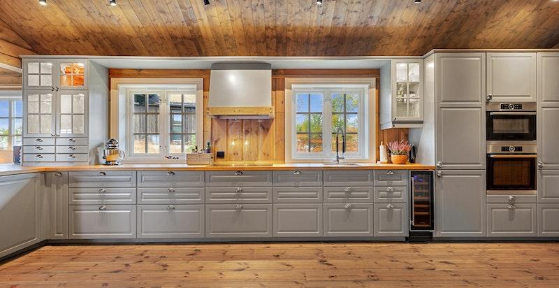 Kjøkkeninnredning med grå profilerte fronter på skuffer og skap.
