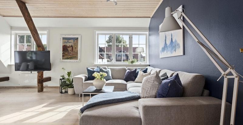 Stuen har sjarmerende vinduer, god takhøyde og hyggelig peis.