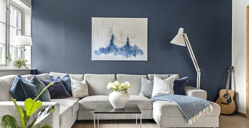 Stuen har en flott kontrastvegg malt i en behagelig blåtone.