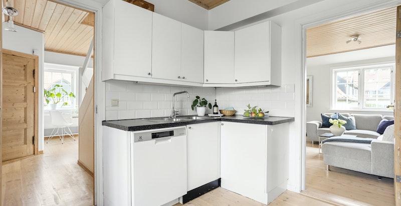 Kjøkkenet har både tilknytning til stuen og boligens entré.