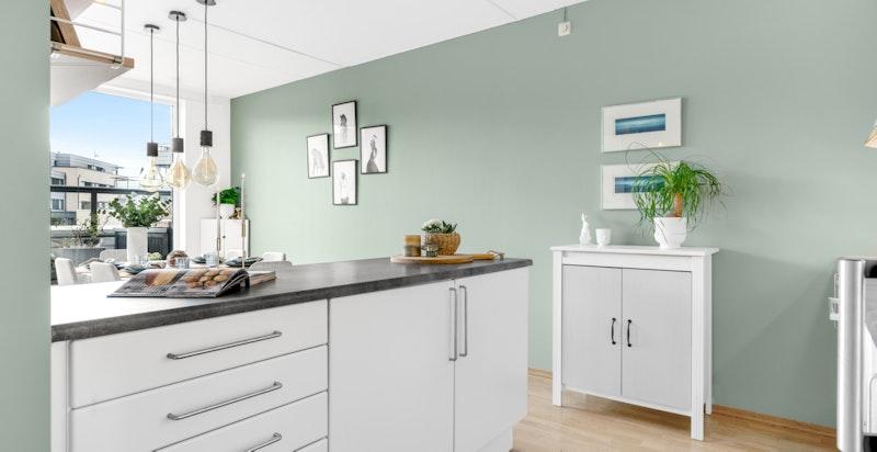 Kjøkkenet er utstyrt med rustfri oppvaskkum, ettgreps blandebatteri, hvite fliser over benk og benkebelysning.