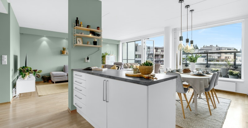 Pent og tidløst kjøkken fra Sigdal med hvite glatte fronter kombinert med grå laminat benkeplate.