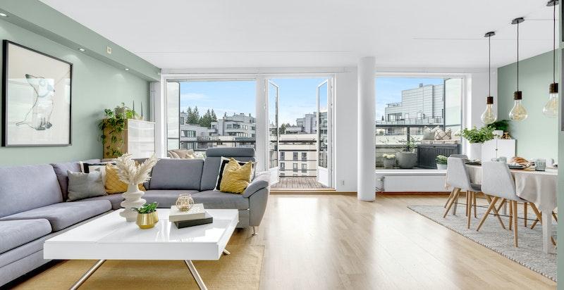 Stuen er romslig og luftig med store vindusflater som bidrar med rikelig naturlig lys.