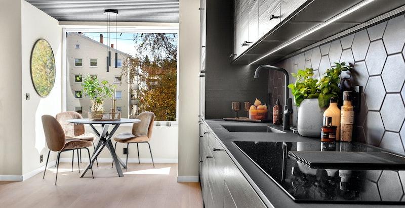 Det er åpen løsning mot rålekkert kjøkken fra Epoq med helsort innredning og utstyr.