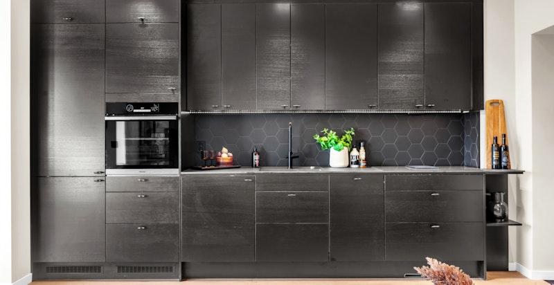 Kjøkkenet praktisk utformet med takhøye overskap og fine arbeidsflater.