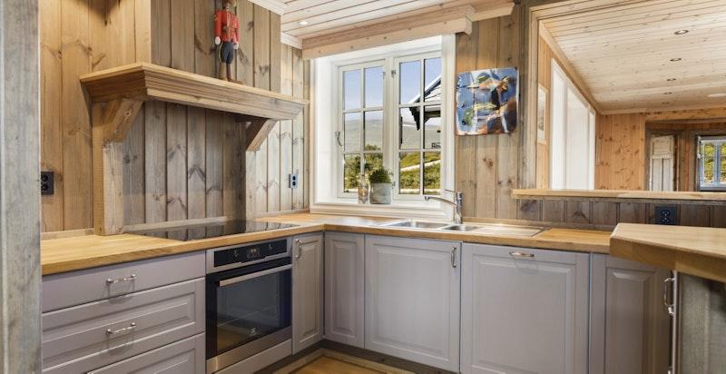 Kjøkkenet har pen innredning med fronter i delikat gråfarge, samt heltre benkeplater i eik
