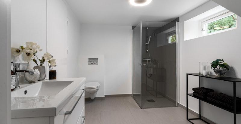 I kjelleren er det et stort, flislagt baderom. På innsiden av dette har du i tillegg vaskerom med oppbevaringsmuligheter