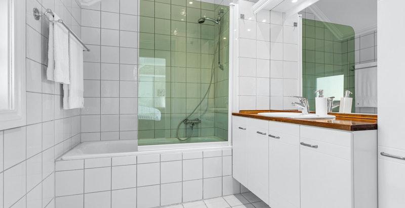Pent og tidløst flislagt bad med gulvvarme, badekar og innredning.