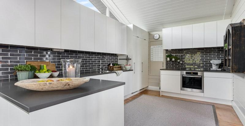 Lys og tidsriktig kjøkkeninnredning med stort lagerrom bak kjøkken.
