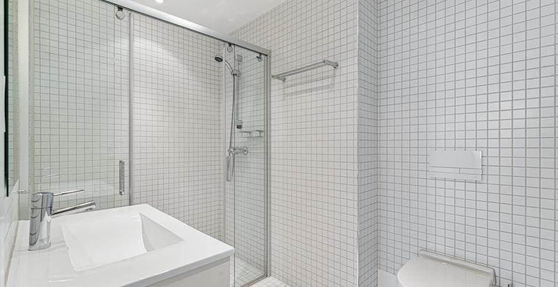 Bad tilknyttet hovedsoverom med fliser på gulv og vegg samt dusj. Varmekabler i gulv.
