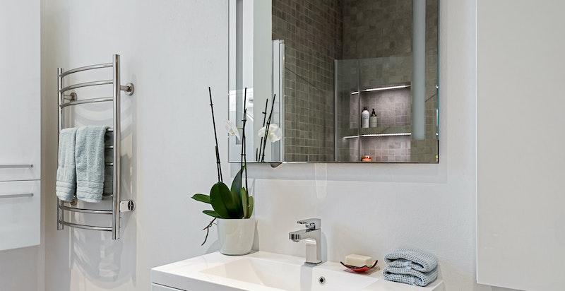 Badet er delikat med en tidsriktig innredning med blant annet regnfallsdusj, heldekkende servant og varmekabler i gulvet.