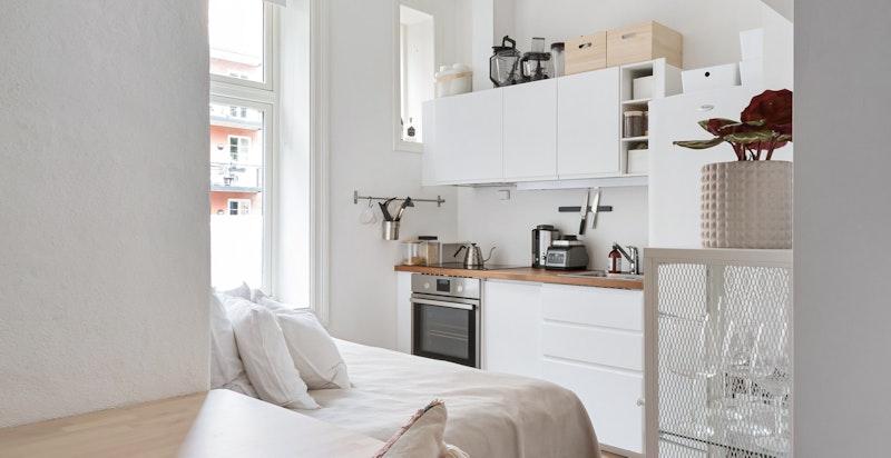 Kjøkkeninnredning fra 2016 med glatte hvite skapfronter. Koketopp, stekeovn og oppvaskmaskin er integrert i innredningen. Kjøl/frys er plassert mot enden av innrednignen.